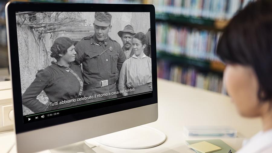 学生看着图书馆的电脑显示器,上面显示着一群人的老照片。