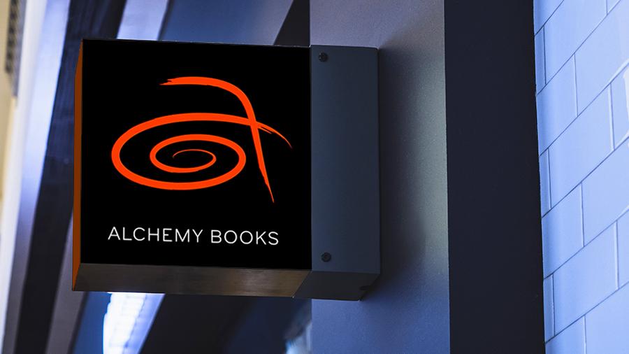 """户外数字标牌在字母下方显示了一个红色的程式化徽标,并标有字母"""" a""""和商店名称"""" Alchemy Books"""""""