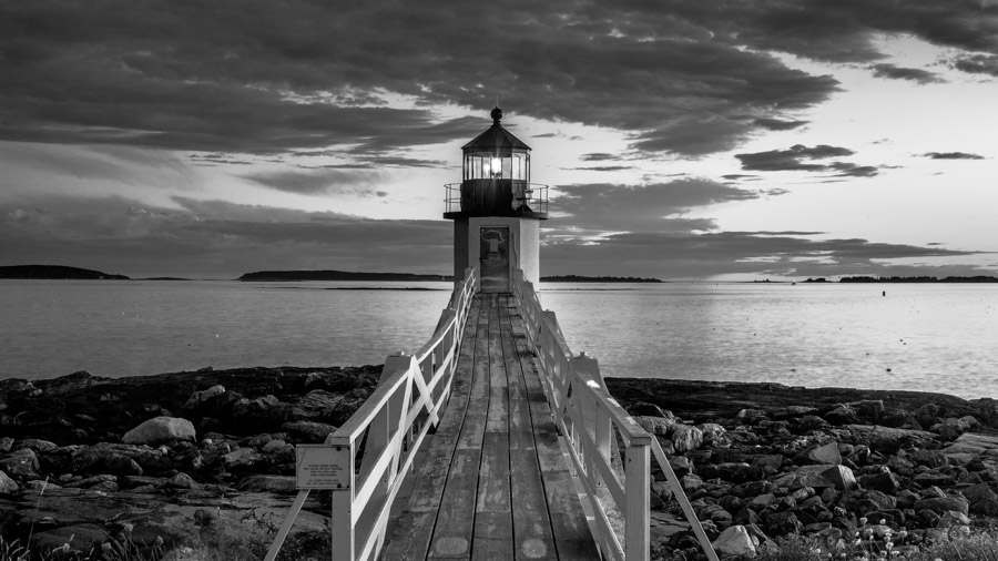 Black and white image of a lighthouse at the end of a deck overlooking the sea