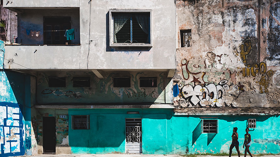 Photo of two people walking by a dilapidated and colorful building with graffiti