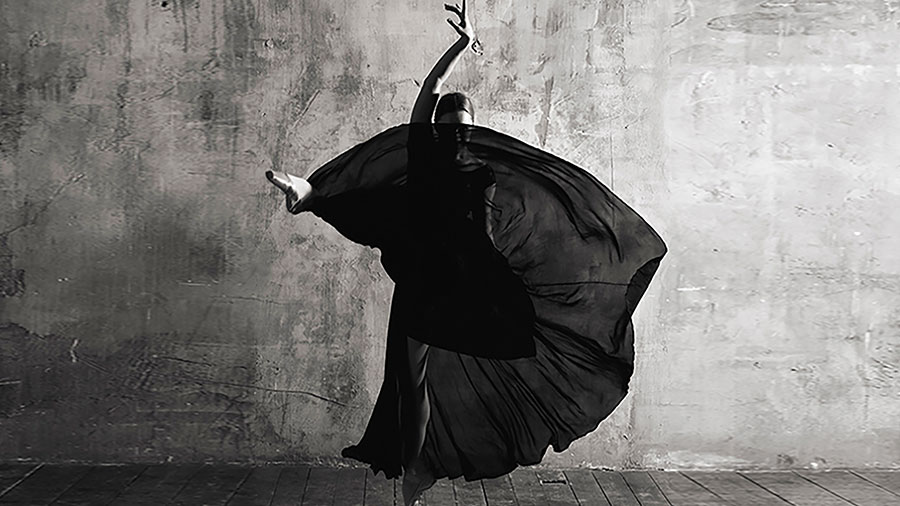 Black and white photograph of a dancer in a long dress striking a dramatic pose