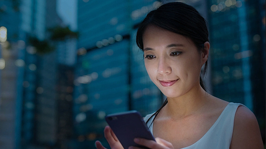 A woman's face lit up by the light from the phone she is looking into