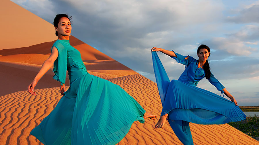 Two women dancing barefoot in front of a sand dune in blue dresses