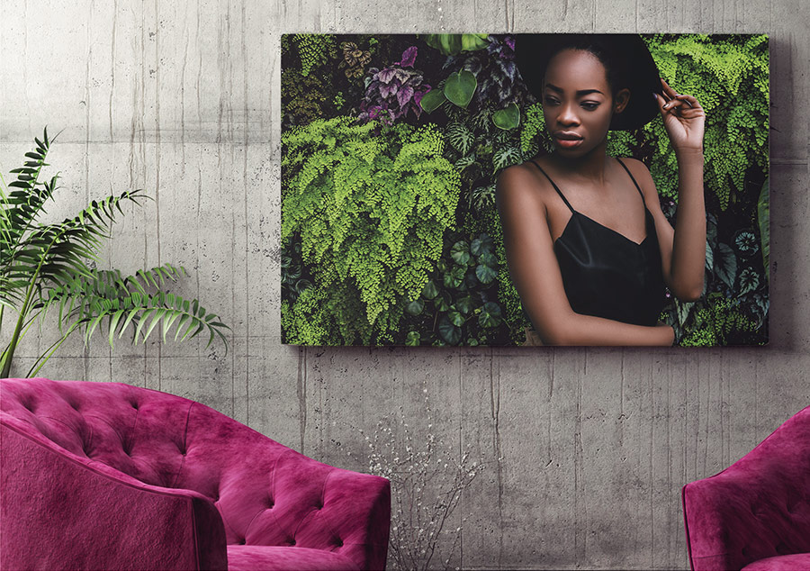 Picture of model in front of new background with green plants placed on a wall behind two fuchsia-colored chairs