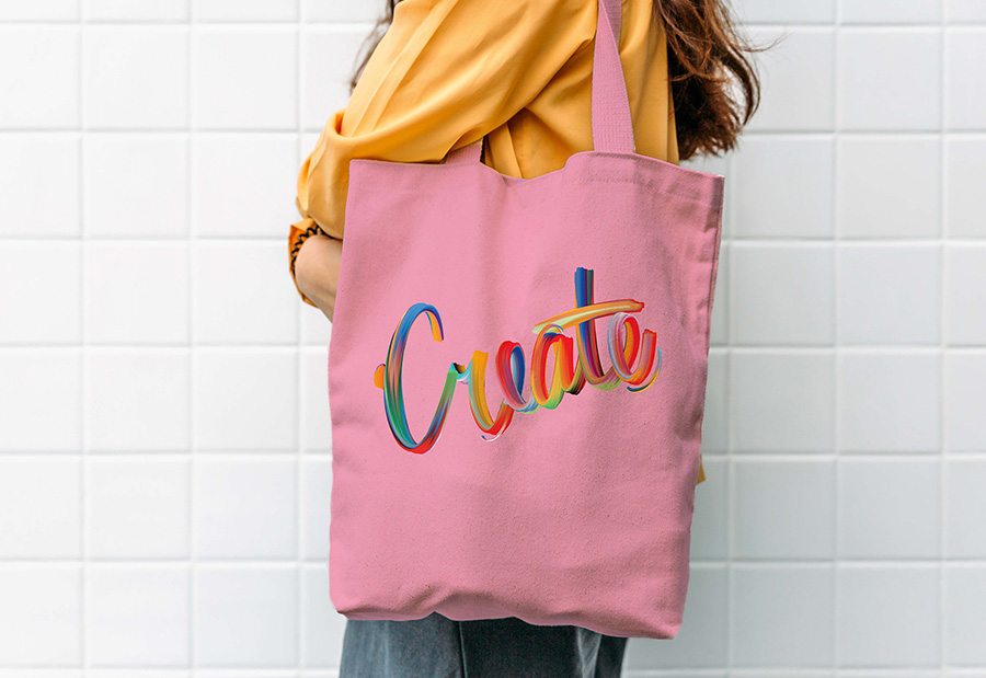 Hand lettering composition displayed on a pink bag on a model's shoulder
