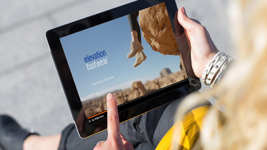 Woman holds tablet that displays ad for Elevation Footwear where a hiker sits on a high ledge in a rocky landscape