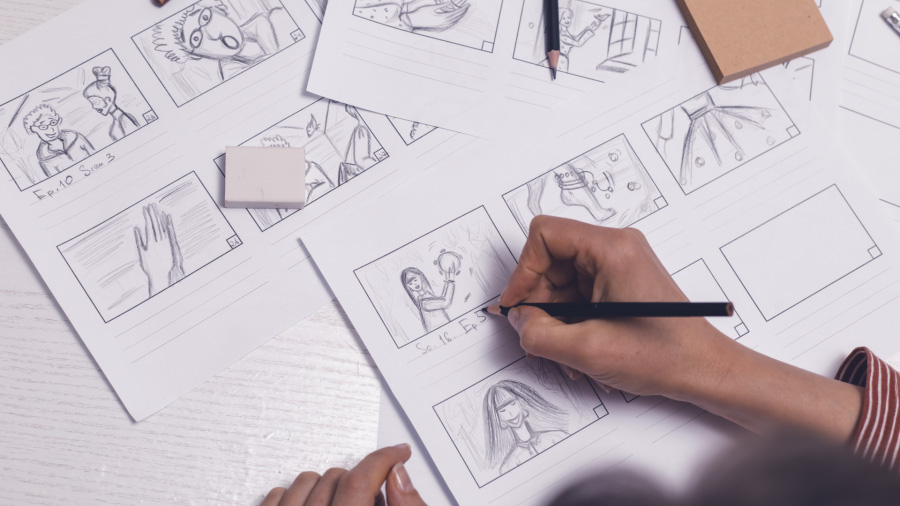 An image of person hand sketching several storyboards depicting a scene