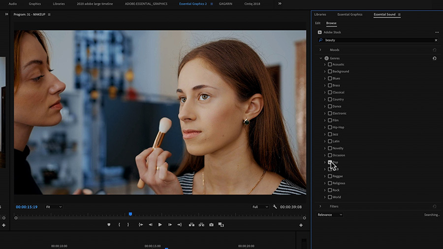 In an Adobe Premiere Pro desktop screenshot, the Program Monitor shows one young Caucasian woman applying makeup to the face of another, and the cursor hovers over the Pop button in the Genre filter in the Essential Sound panel with the term 'beauty' entered into the search bar