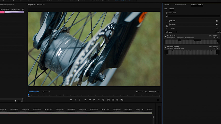 In an Adobe Premiere Pro desktop screenshot focused on both the Program Monitor, which shows a close up on the hub of a mountain bike, and the Essential Sound panel, the editor has is hovering their cursor over the filter by genre option in the Essential Sound panel