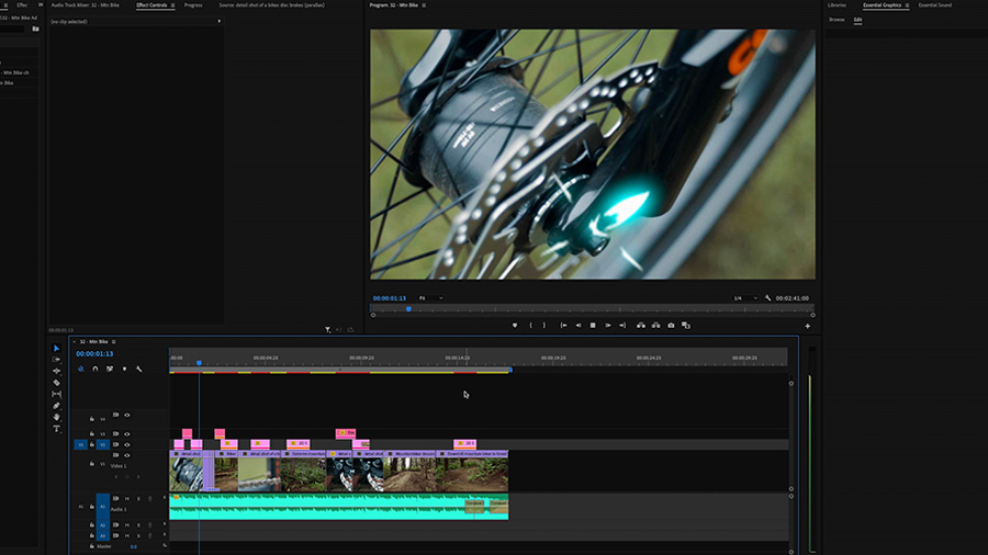In an Adobe Premiere Pro desktop screenshot a close up on a mountain bike hub with a glowing animated graphic is sitting above the timeline with a short edited film cut on three video tracks and one audio track