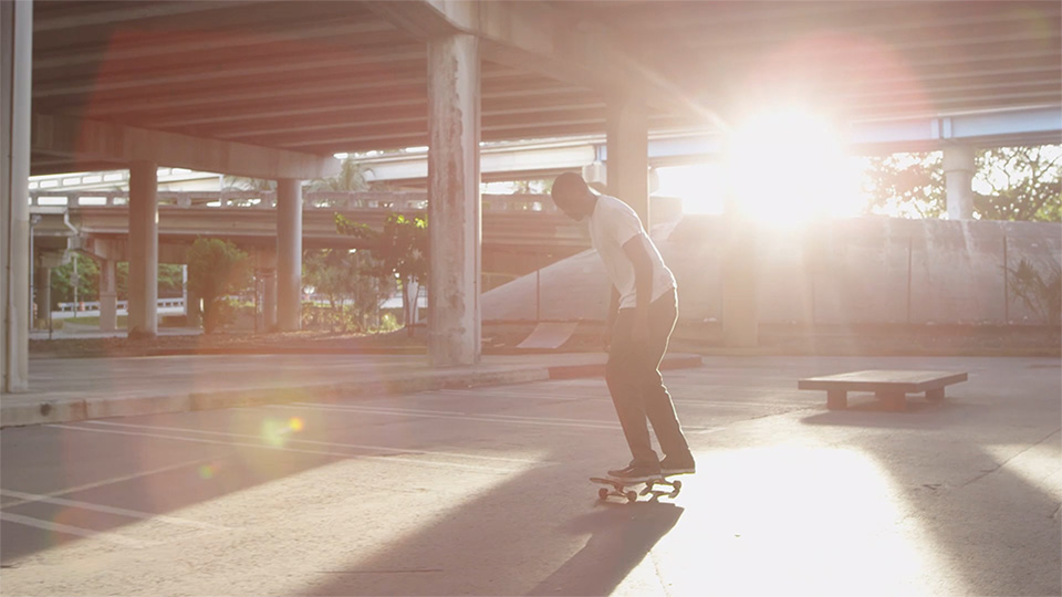 A young African American man rides a skateboard in an empty covered parking garage as the sun shines into the camera