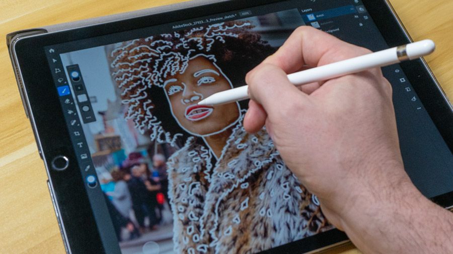 Photo of a woman loaded into Photoshop on the iPad with a hand tracing over the image using the brush tool