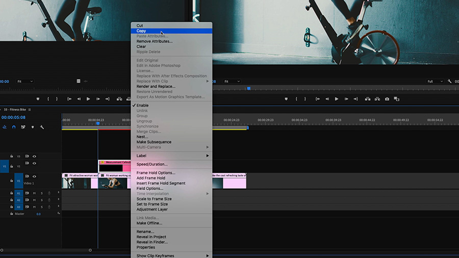 In an Adobe Premiere Pro desktop screenshot, the editor has control+clicked on the 'Measurement Callouts' Motion Graphics template in V2 of the timeline, revealing a pop-up dialogue box where the cursor is highlighting the word 'Copy' and an edit of a woman riding a stationary bike can be seen in the background